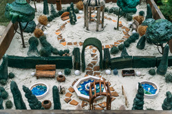Miniature houses, toy landscape objects in sandbox. Anti-stress and soothing sand therapy