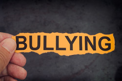 Person holds piece of paper with word Bullying in his hand.jpg Close up