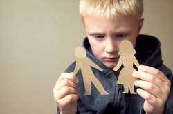 Confused child with cutting paper parents, family problems, divorce, custody battle, suffer concept_