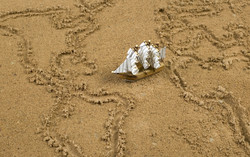 Miniature ship on sand which pictures global map with continents and oceans