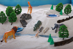 Miniature family constellations, toy zoo. Sand therapy. The child is built in a sandbox world, the a