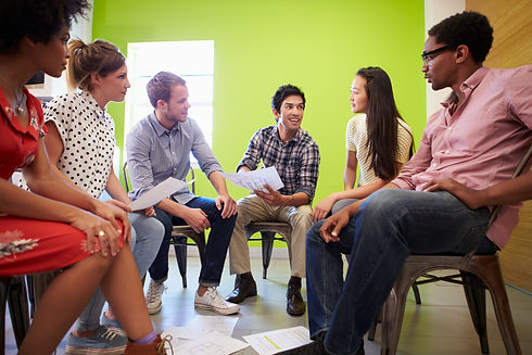 A group of young adults sitting in a circle smiling and listening to one another.