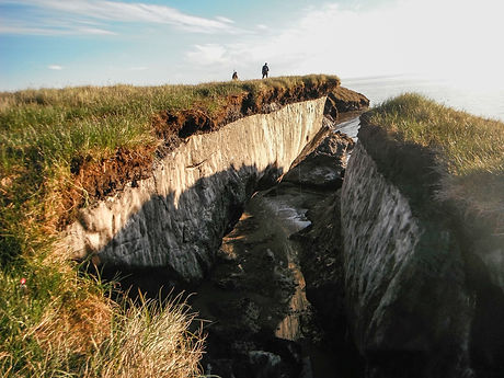 The frozen soils of the permafrost are exposed after a storm along the coastline of Barter Island in