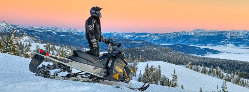 Snowmobiler on Mountain Looking At Sunset