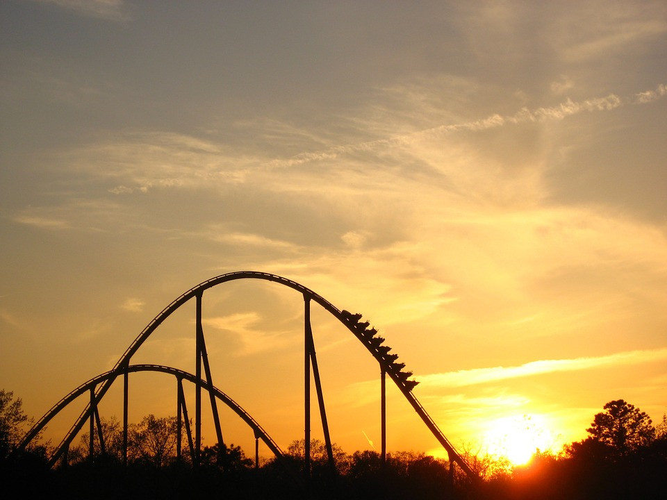 Roller Coaster At Theme Park With Sunset
