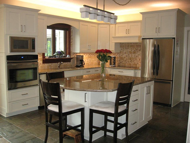 White painted shaker style cabinets with Travertine Backsplash and granite countertops