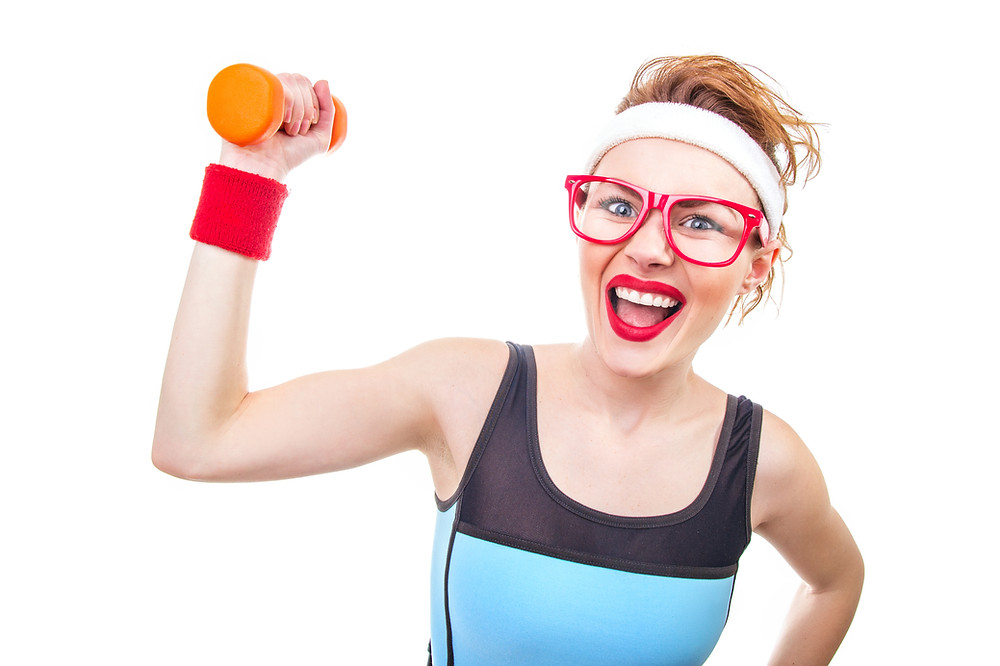 Woman in a whacky 1980ies aerobic outfit with a dumbell in one hand
