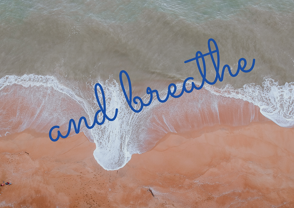 "Waves break on a sandy beach with a sign ""and breathe"""