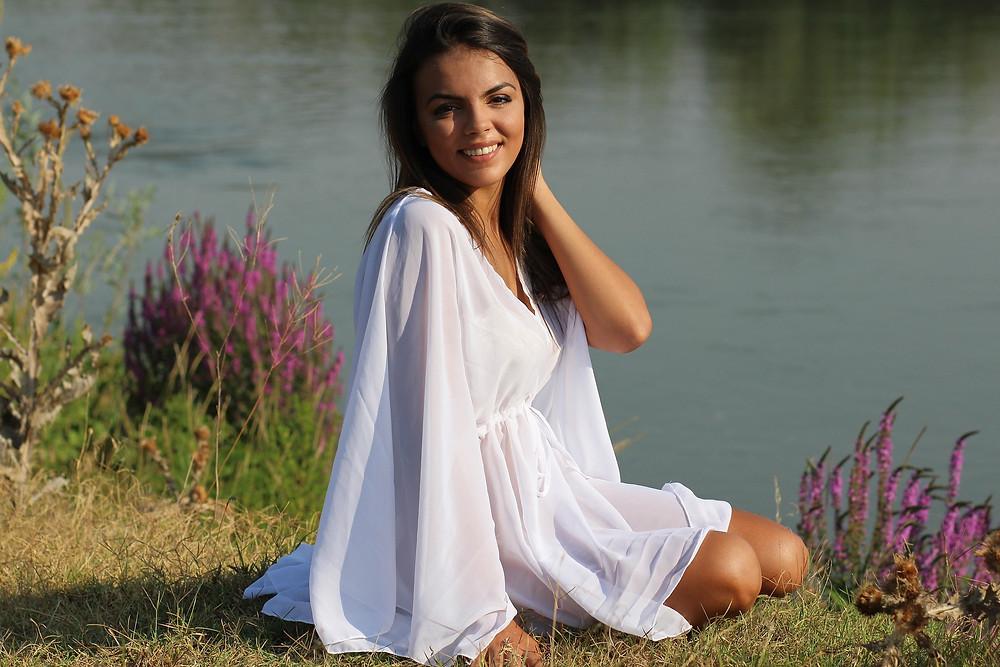 Junge Frau in fliessendem weissen Kleid am See