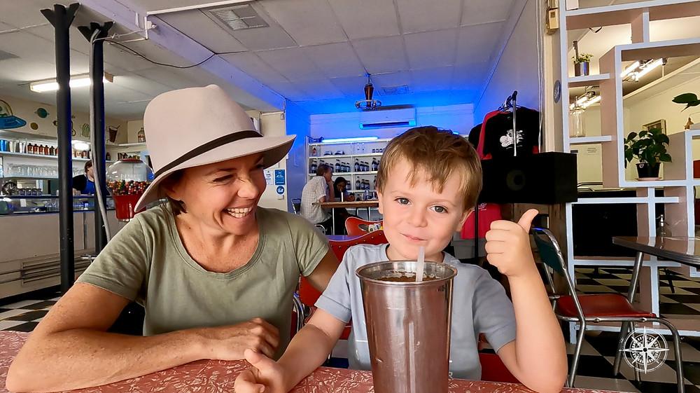 Mother and son enjoying a milkshake, old school milk bar