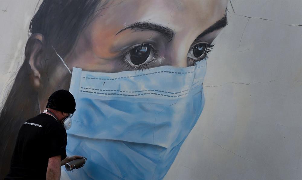 O grafiteiro Bram De Ceurt trabalha no desenho de uma enfermeira protegida contra o coronavírus com uma máscara na Antuérpia, Bélgica — Foto: Virginia Mayo/AP