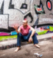 Composer and Sound Artist, Peter Falconer, sitting barefoot in a tunnel, with a pink mohawk, like a totally stylish and credible artist.