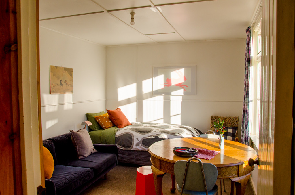 The main room- with a couch, dining area for 3 and single bed.