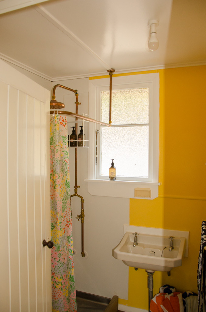 The tiny bathroom fitted with copper shower, a toilet and beautiful ashley & co products.