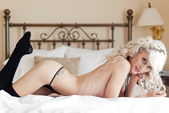 sexy boudoir with woman in thigh high socks laying on bed