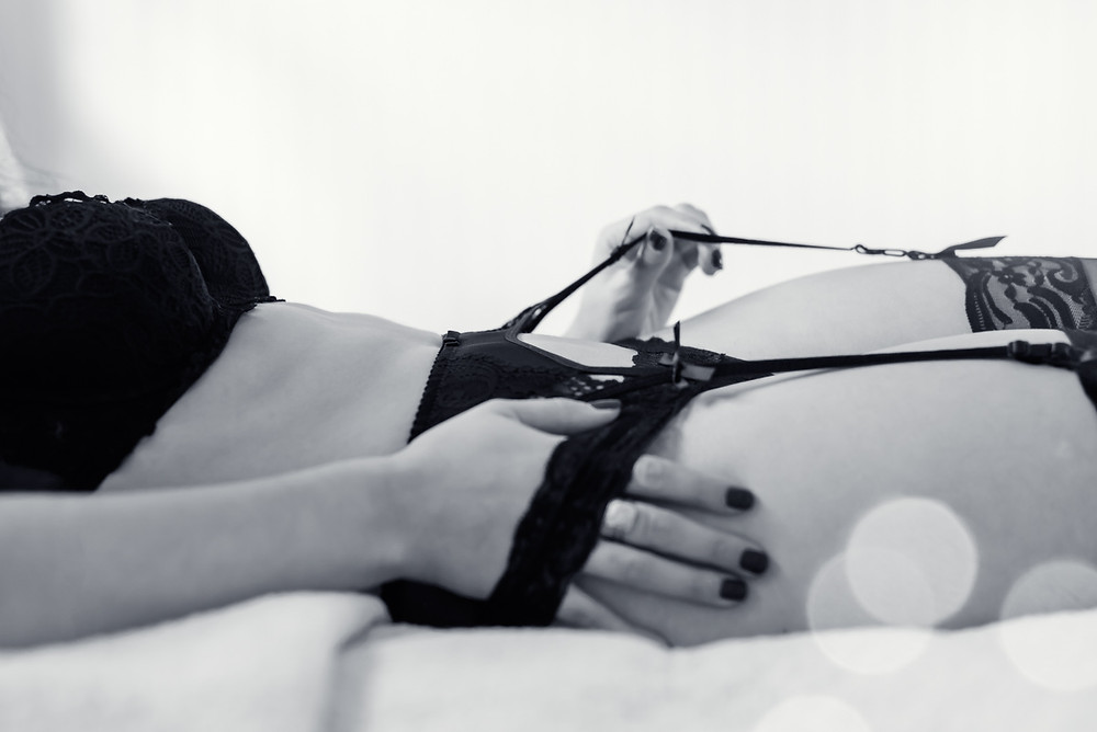boudoir photo of woman in black lingerie laying in bed grabbing garter belt