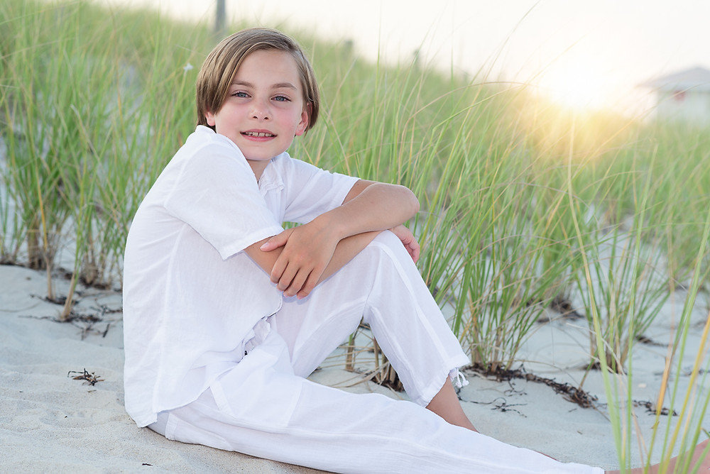 young person sitting near beach grass