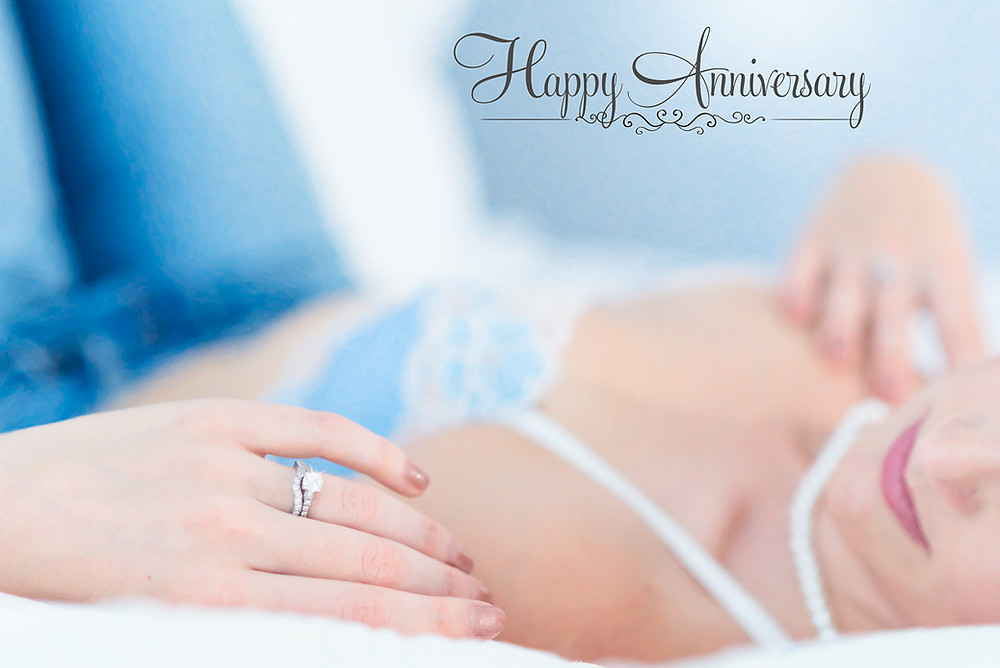 boudoir photo of woman's engagement ring laying in bed