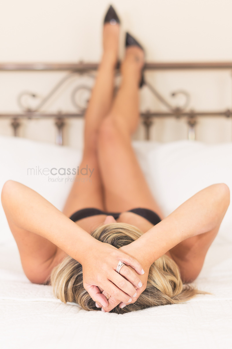 boudoir photo of a woman laying back with her legs up on a headboard