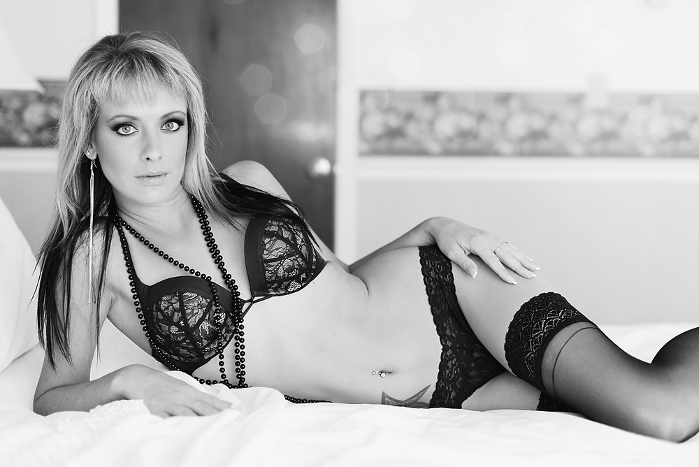 boudoir photo of attractive woman in sexy black lingerie laying in bed
