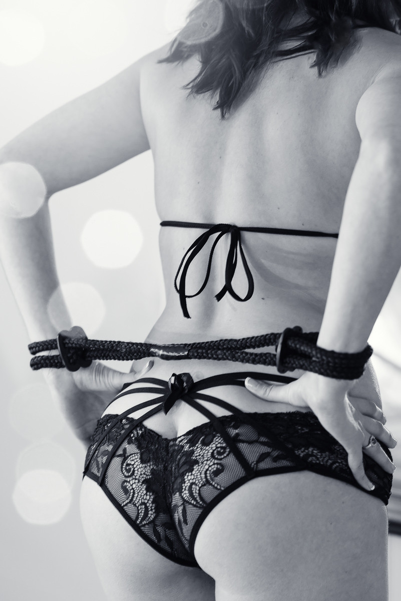 hot boudoir pose of woman with hands restrained behind back