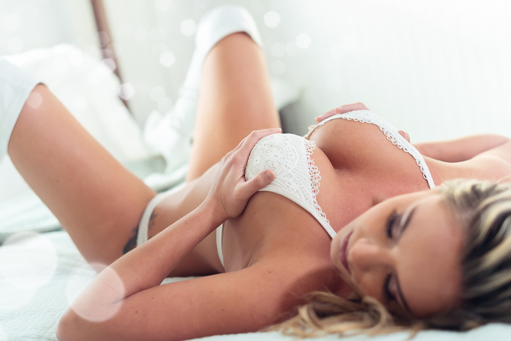 boudoir photo of woman laying in bed in lingerie