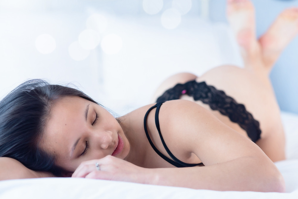 boudoir photo of woman laying in bed in underwear pushing her booty up in the air.