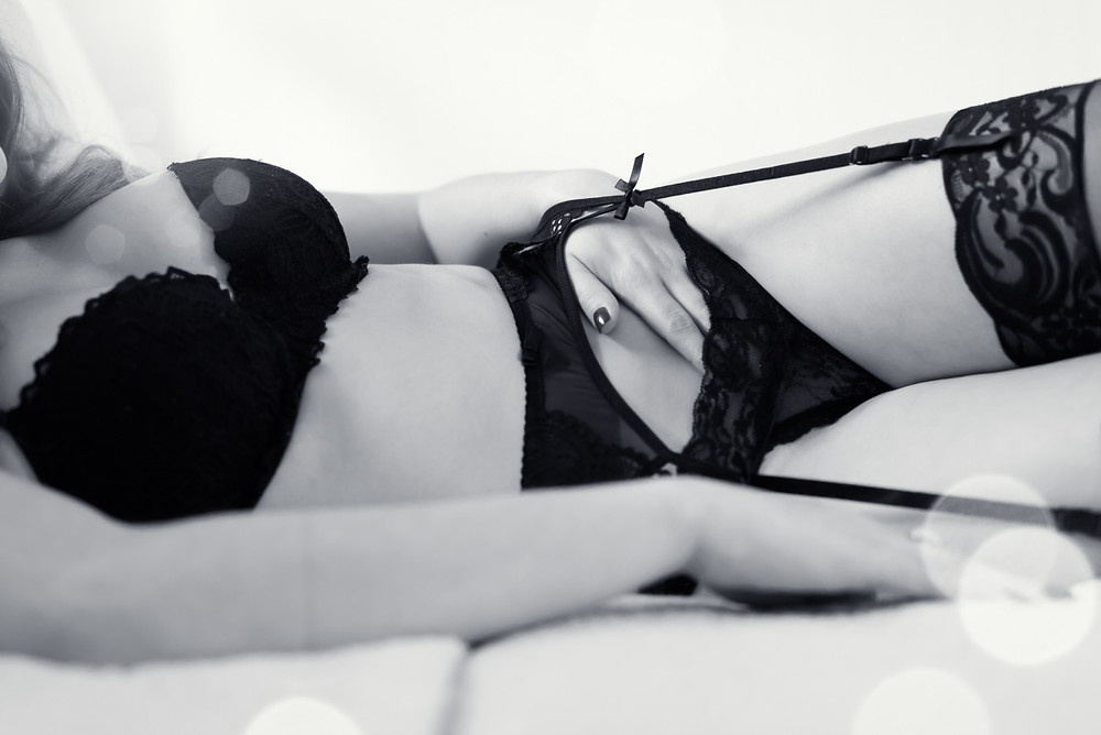boudoir photo of a woman laying in bed in black lingerie