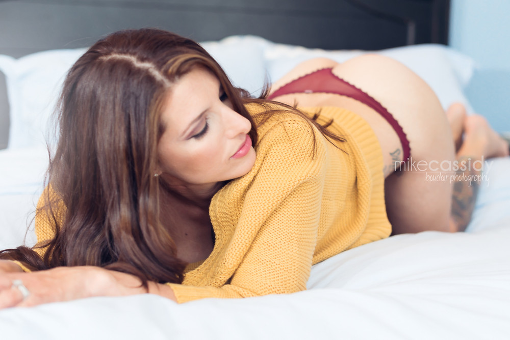 boudoir photo of a woman in bed wearing a sweater looking over her shoulder