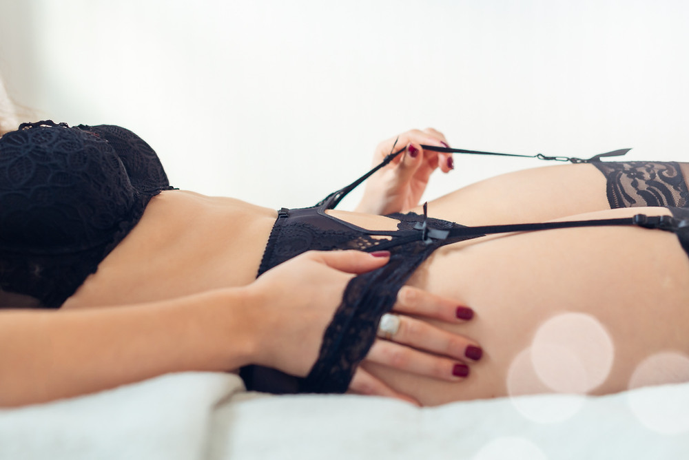 woman laying in bed in black lingerie doing a boudoir photography pose