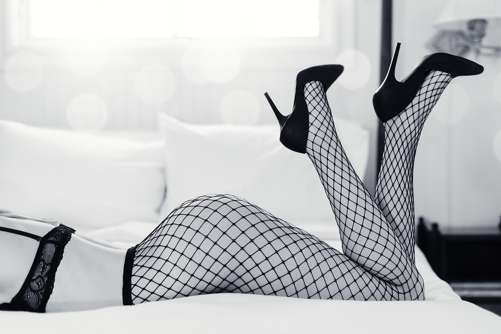 boudoir pose of a woman laying in bed in fishnets and heels