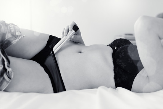 boudoir photo of woman in bed in underwear with vibrator