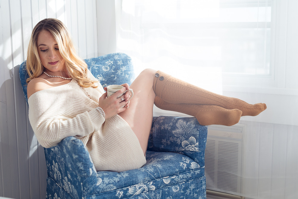 boudoir photo of a blonde woman in a sweater and knee socks sitting in a chair holding a coffee cup