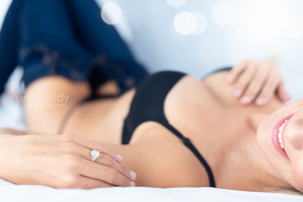 boudoir photo of woman laying in bed in black underwear smiling
