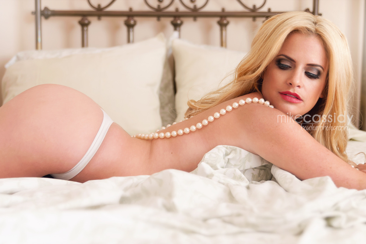 boudoir pose with beautiful blonde laying in bed.