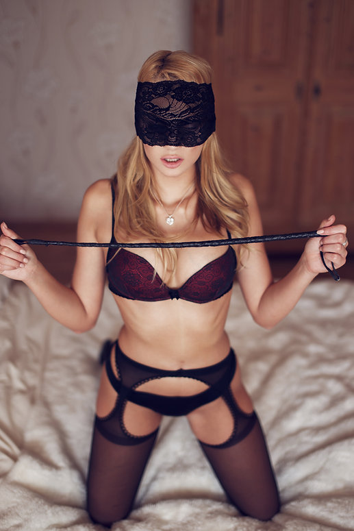erotic boudoir woman with whip and blindfold