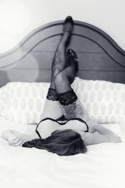 boudoir pose with legs up on bed