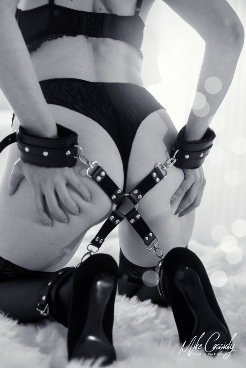 black and white boudoir shot of woman on knees with hogtie behind back.