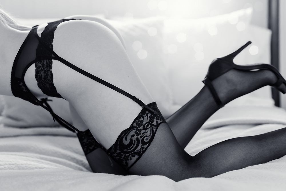 boudoir photo of woman in black lingerie, stockings, and heels on a bed