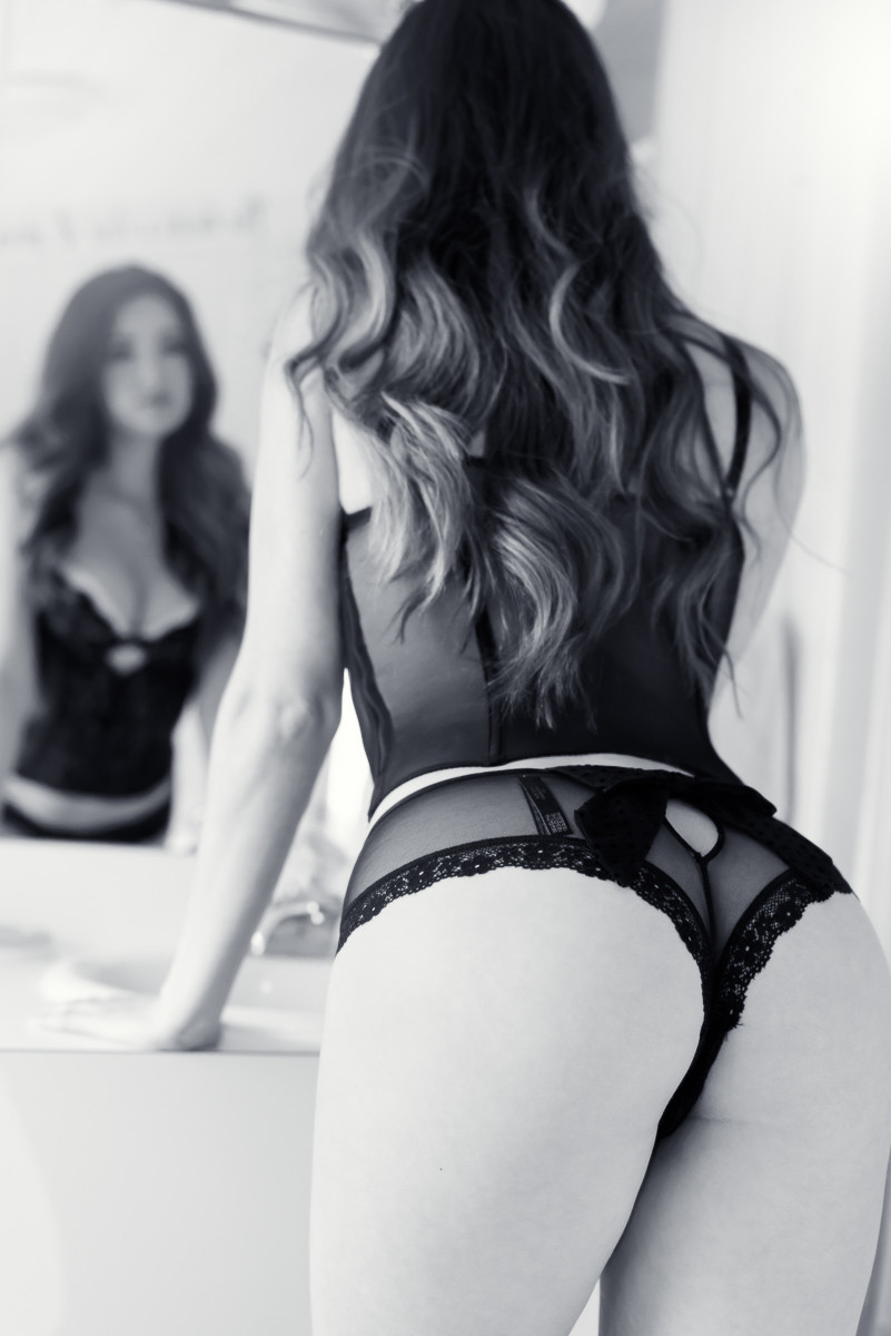 boudoir photo of a stunning brunette looking into a mirror in lingerie