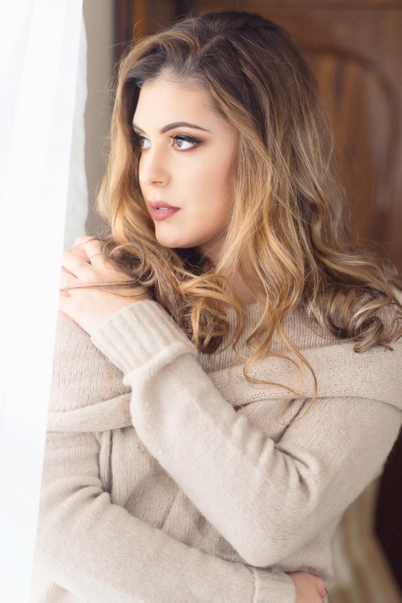 woman wearing a beige sweater gazing out a window