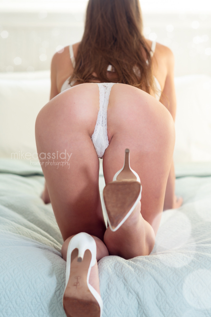 boudoir photo of a woman crawling on to a bed