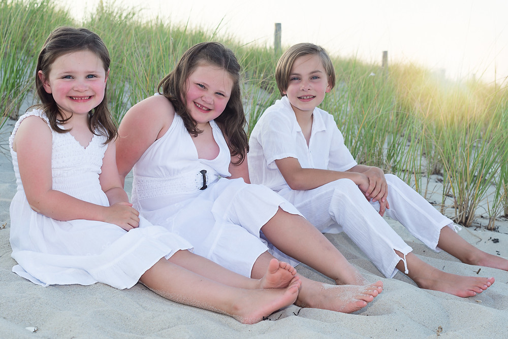 three children sitting near dune grass on the beach at sunset