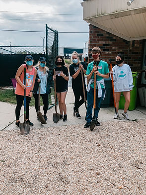 Volunteers from PAALS stand next to each other with shovels in the play yards with gravel