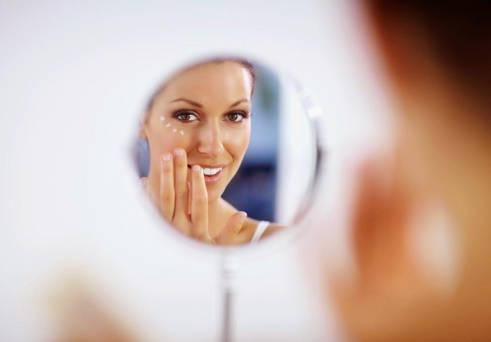 A woman applying facial cream in a mirror