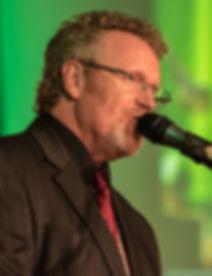 Craig_on_stage_goat_green_background_edi
