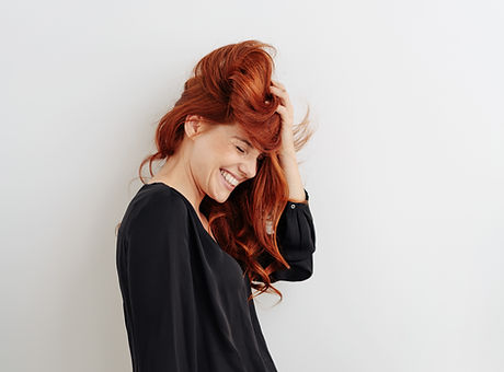 Fun young woman with tousled red hair gi