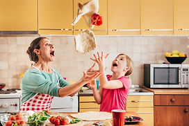 Mother and daughter preparing pizza in t