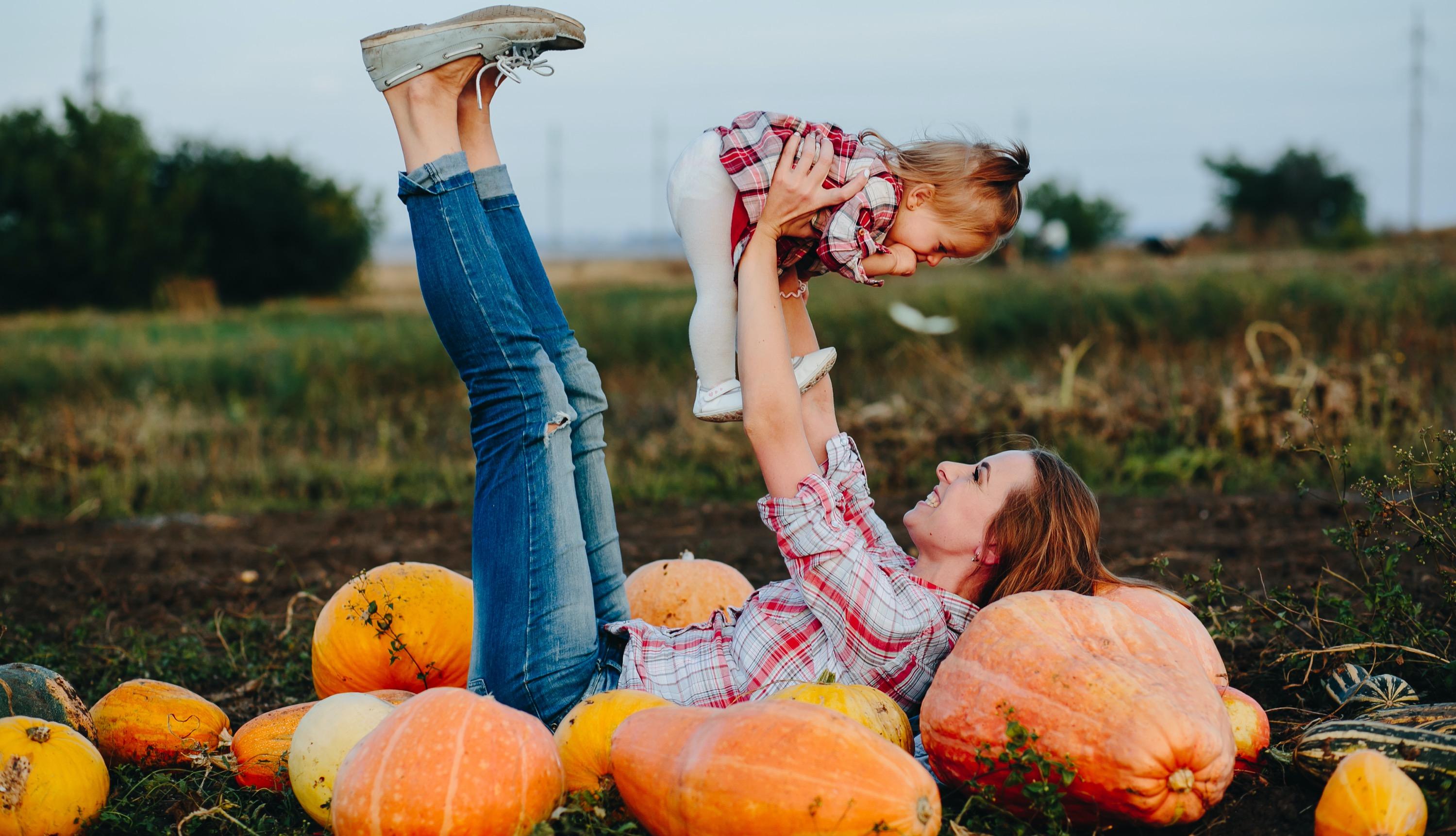 mother-and-daughter-lie-between-pumpkins