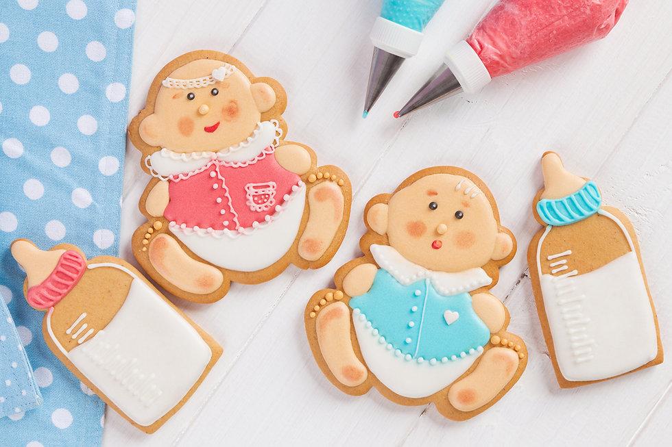 Decoração com objetos de bebê, incluindo pequenos bonecos rosa e azul